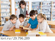 Купить «Female librarian and schoolkids during classes in library», фото № 29796289, снято 19 декабря 2018 г. (c) Яков Филимонов / Фотобанк Лори