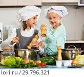 Купить «Two small happy girls cooking vegetable soup», фото № 29796321, снято 22 февраля 2019 г. (c) Яков Филимонов / Фотобанк Лори