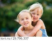 Купить «Two smiling little girls embracing», фото № 29796337, снято 20 июля 2017 г. (c) Яков Филимонов / Фотобанк Лори