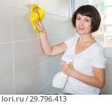 Купить «Woman cleaning tiled wall», фото № 29796413, снято 22 ноября 2018 г. (c) Яков Филимонов / Фотобанк Лори