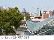 Мост Мира — пешеходный мост через реку Мтквари (Кура) в Тбилиси. На дальнем плане собор Сиони (2013 год). Редакционное фото, фотограф Олег Хархан / Фотобанк Лори