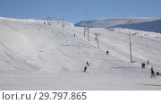 Купить «Ski resort in Khibiny. Skiers and snowboarders ascend on the ski lift and go down the slope», видеоролик № 29797865, снято 11 марта 2016 г. (c) Юлия Бабкина / Фотобанк Лори