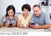 Купить «Relatives using mobile phones», фото № 29813365, снято 27 марта 2019 г. (c) Яков Филимонов / Фотобанк Лори
