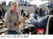 Купить «Mature man looking vintage souvenirs at flea market», фото № 29813469, снято 23 октября 2017 г. (c) Яков Филимонов / Фотобанк Лори