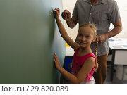 Купить «Schoolgirl with math teacher looking at camera and writing on chalk board in classroom», фото № 29820089, снято 10 ноября 2018 г. (c) Wavebreak Media / Фотобанк Лори