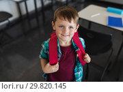 Купить «High angle view of happy schoolboy with schoolbag looking at camera in classroom», фото № 29820145, снято 10 ноября 2018 г. (c) Wavebreak Media / Фотобанк Лори