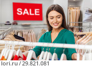 Купить «happy woman choosing clothes at clothing store», фото № 29821081, снято 19 февраля 2016 г. (c) Syda Productions / Фотобанк Лори