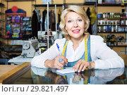 Купить «Tailor taking order at counter», фото № 29821497, снято 23 февраля 2019 г. (c) Яков Филимонов / Фотобанк Лори