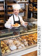 Купить «Skillful male pastry maker demonstrating croissant», фото № 29821597, снято 26 января 2017 г. (c) Яков Филимонов / Фотобанк Лори