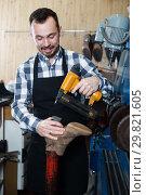 Купить «Positive man worker working at restoring boots», фото № 29821605, снято 2 февраля 2017 г. (c) Яков Филимонов / Фотобанк Лори