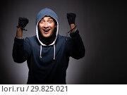 Купить «Young gangster in hood on grey background», фото № 29825021, снято 27 сентября 2018 г. (c) Elnur / Фотобанк Лори