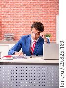 Купить «Young handsome employee working in the office», фото № 29825189, снято 12 сентября 2018 г. (c) Elnur / Фотобанк Лори