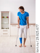 Купить «Leg injured young man with crutches at home», фото № 29825677, снято 19 сентября 2018 г. (c) Elnur / Фотобанк Лори