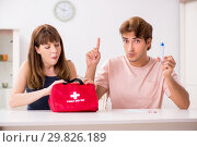 Купить «Young family getting treatment with first aid kit», фото № 29826189, снято 24 августа 2018 г. (c) Elnur / Фотобанк Лори