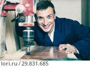 Купить «Man operating automatic screwdriver in wood workshop», фото № 29831685, снято 27 мая 2019 г. (c) Яков Филимонов / Фотобанк Лори
