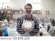 Купить «Proud male potter showing his creation to camera», фото № 29839225, снято 6 августа 2017 г. (c) Wavebreak Media / Фотобанк Лори