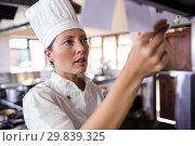 Купить «Female chef looking at order list in kitchen», фото № 29839325, снято 15 марта 2016 г. (c) Wavebreak Media / Фотобанк Лори