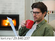 Купить «Man reading newspaper while having coffee in living room», фото № 29840237, снято 3 августа 2017 г. (c) Wavebreak Media / Фотобанк Лори