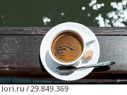 Купить «A small white porcelain espresso cup on a saucer with a teaspoon and two pieces of sugar», фото № 29849369, снято 17 июня 2017 г. (c) katalinks / Фотобанк Лори