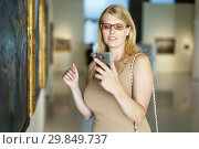 Купить «Female visitor taking picture in museum», фото № 29849737, снято 22 сентября 2018 г. (c) Яков Филимонов / Фотобанк Лори
