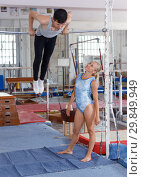 Купить «Man and woman doing acrobatic exercises in gym», фото № 29849949, снято 18 июля 2018 г. (c) Яков Филимонов / Фотобанк Лори