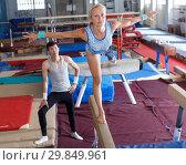 Купить «Woman acrobat in bodysuit exercising action at broad bars in gym, man helping», фото № 29849961, снято 18 июля 2018 г. (c) Яков Филимонов / Фотобанк Лори