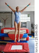 Купить «Woman gymnast in bodysuit jumping at trampoline in sport gym», фото № 29849965, снято 18 июля 2018 г. (c) Яков Филимонов / Фотобанк Лори