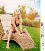 Youmg beautiful woman in beautiful summer garden is On the wicker lounger. Стоковое фото, фотограф katalinks / Фотобанк Лори