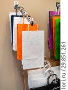 Купить «Multicolored paper bags hang on a hanger», фото № 29851261, снято 17 июня 2016 г. (c) Андрей Радченко / Фотобанк Лори