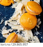 Купить «Whole and broken orange lemon homemade macaroons with chopped white chocolate and citrus sugar and zest on dark glass board over black textural background. Overhead view. Square image», фото № 29865957, снято 6 февраля 2020 г. (c) age Fotostock / Фотобанк Лори