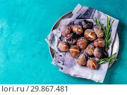 Купить «Roasted chestnuts in the ashes with rosemary in metal plate on paper over bright turquoise wooden background. Top view with space for text.», фото № 29867481, снято 21 ноября 2019 г. (c) age Fotostock / Фотобанк Лори