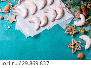 Купить «Homemade Christmas nuts cookies crescent on white baking paper with sugar powder in holiday decoration and fir tree over turquoise wood texture surface. Top view. Christmas background theme.», фото № 29869837, снято 22 февраля 2020 г. (c) age Fotostock / Фотобанк Лори