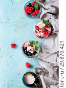 Купить «Traditional summer dessert Eton Mess. Broken meringue with whipped cream, berry jam, fresh blueberries and raspberries in two glasses, decorated with mint leaves over light blue concrete background.», фото № 29870421, снято 12 июля 2020 г. (c) age Fotostock / Фотобанк Лори