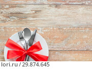 Купить «cutlery tied with red ribbon on set of plates», фото № 29874645, снято 9 февраля 2018 г. (c) Syda Productions / Фотобанк Лори