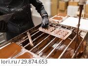 Купить «confectioner removing excess chocolate from mold», фото № 29874653, снято 4 декабря 2018 г. (c) Syda Productions / Фотобанк Лори