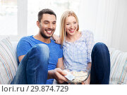 happy couple with popcorn watching tv at home. Стоковое фото, фотограф Syda Productions / Фотобанк Лори