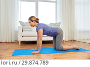 Купить «woman doing yoga cow pose at home», фото № 29874789, снято 13 ноября 2015 г. (c) Syda Productions / Фотобанк Лори