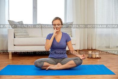 woman doing yoga breathing exercise in lotus pose