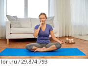 woman doing yoga breathing exercise in lotus pose. Стоковое фото, фотограф Syda Productions / Фотобанк Лори