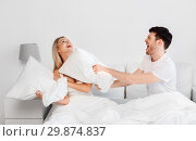 happy couple having pillow fight in bed at home. Стоковое фото, фотограф Syda Productions / Фотобанк Лори