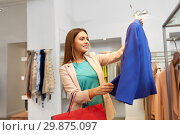 Купить «happy woman choosing clothes at clothing store», фото № 29875097, снято 19 февраля 2016 г. (c) Syda Productions / Фотобанк Лори