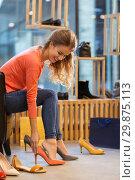 Купить «young woman trying high heeled shoes at store», фото № 29875113, снято 22 сентября 2017 г. (c) Syda Productions / Фотобанк Лори