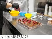 Купить «confectioner makes chocolate dessert at sweet-shop», фото № 29875169, снято 4 декабря 2018 г. (c) Syda Productions / Фотобанк Лори