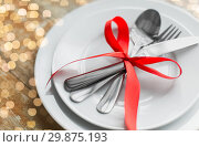 Купить «close up of cutlery tied with red ribbon on plates», фото № 29875193, снято 9 февраля 2018 г. (c) Syda Productions / Фотобанк Лори