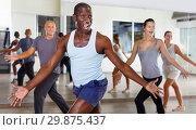 Купить «Cheerful people practicing vigorous lindy hop movements in dance class», фото № 29875437, снято 30 июля 2018 г. (c) Яков Филимонов / Фотобанк Лори