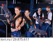 Купить «Two smiling girls posing with plastic laser pistols and two guys in background in laser tag room», фото № 29875617, снято 27 августа 2018 г. (c) Яков Филимонов / Фотобанк Лори
