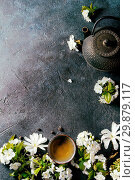 Купить «Traditional ceramic cup of hot green tea with black iron teapot, spring flowers white magnolia and cherry blooming branches over dark blue texture background. Top view, copy space.», фото № 29879117, снято 11 июля 2020 г. (c) age Fotostock / Фотобанк Лори