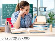 Купить «Female student with many books sitting in the classroom», фото № 29887085, снято 19 ноября 2018 г. (c) Elnur / Фотобанк Лори