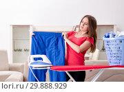 Купить «Young beautiful woman ironing at home», фото № 29888929, снято 30 октября 2018 г. (c) Elnur / Фотобанк Лори