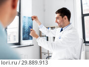 Купить «doctor showing x-ray to patient at hospital», фото № 29889913, снято 25 августа 2018 г. (c) Syda Productions / Фотобанк Лори
